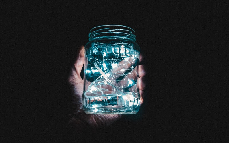 A hand holding a mason jar full of blue battery-powered string lights in the dark.