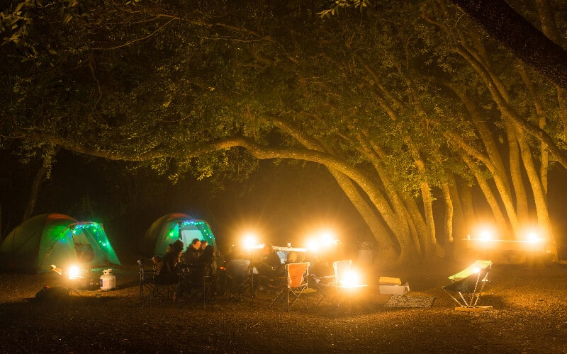 A cluster of camping lanterns illuminating a campsite full of a group of people and two tents.