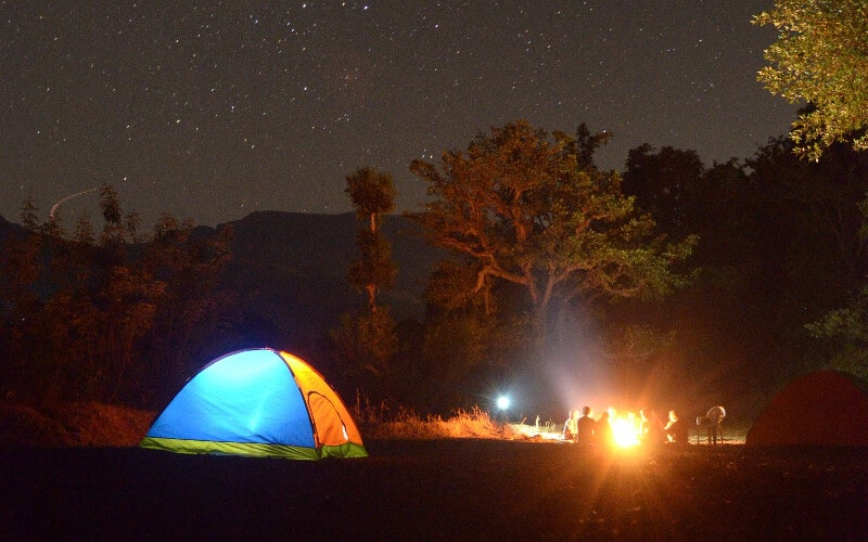 A camping tent lit up next to a group of people around a campfire at night.