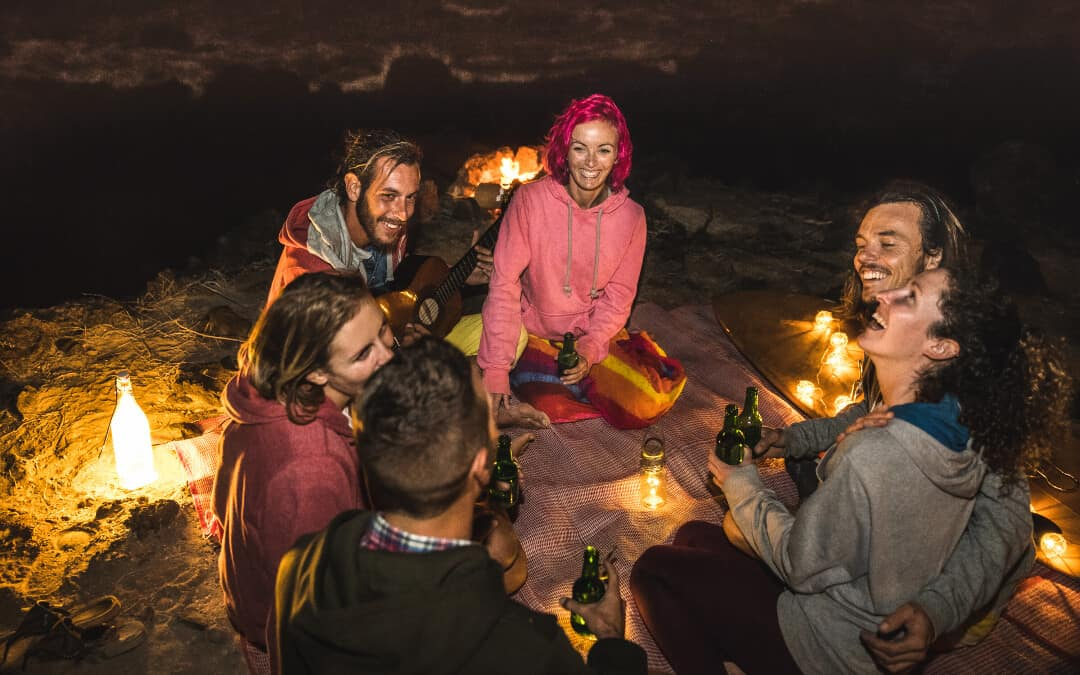 A group of friends having fun on the beach using campsite lighting ideas such as lanterns, fire, and bottles with lights to illuminate their surroundings.