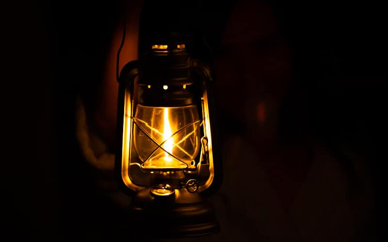 A person holding a fuel lantern in the dark.