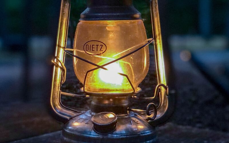 Close up of a gas-powered lantern on a table.