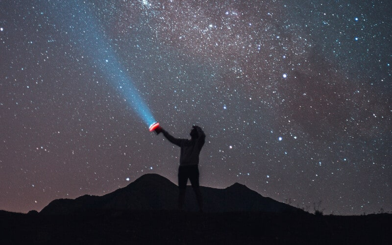 Silhouette of a person holding a flashlight on top of a hill.