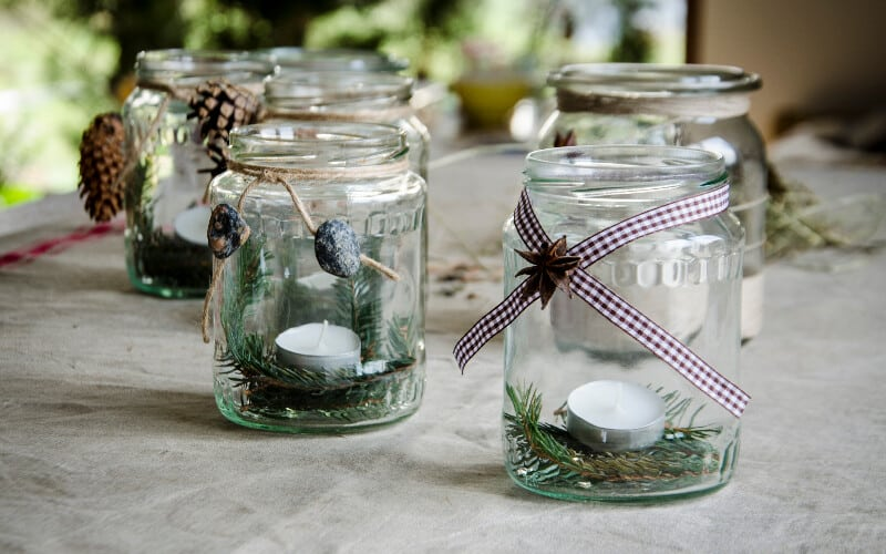Decorated unlit mason jar lanterns sitting on a table.