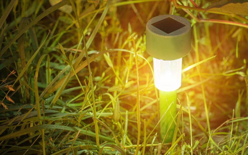 A solar-powered light staked into the ground surrounded by grass.
