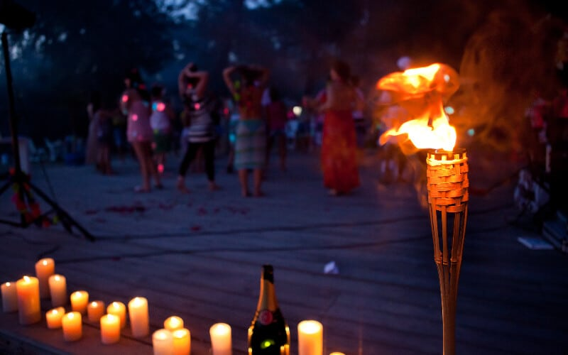 A tiki torch and candles used as camping lighting on a beach with a group of people in the background.