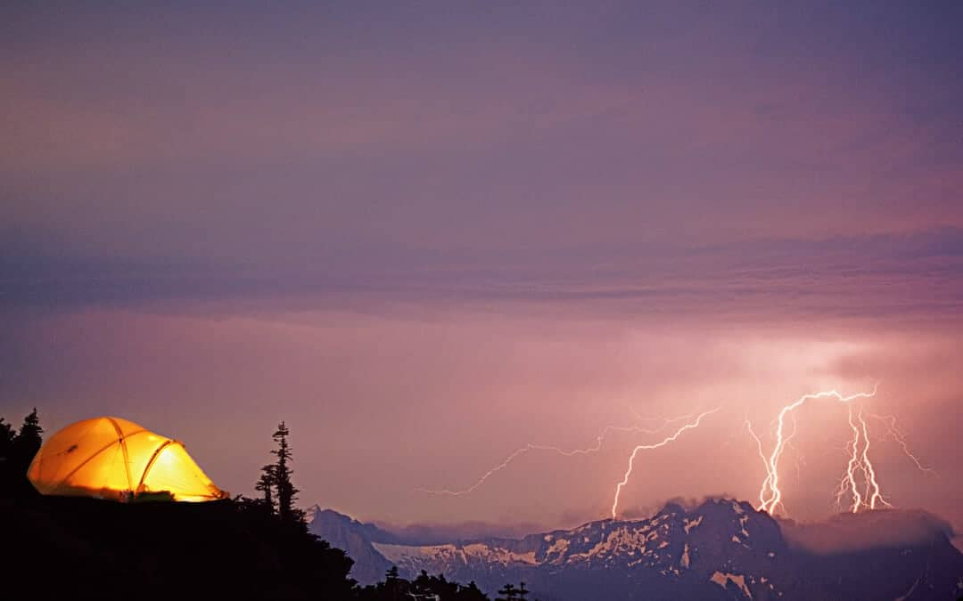 A tent full of people camping in a thunderstorm, with lightning on the horizon.
