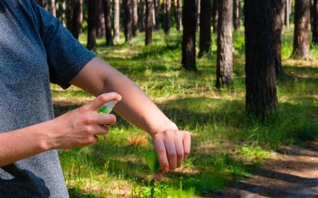 Camping Insect Repellent Banner: A person spraying bug spray on their arm to repel mosquitos and pests.
