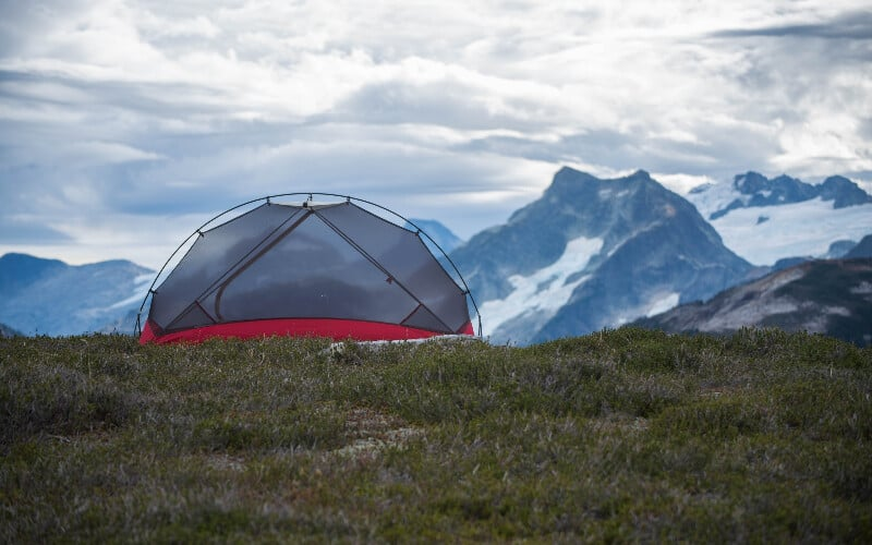 A bug-proof tent in front of a mountain.