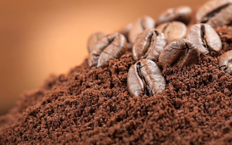 Coffee beans laying on top of coffee grounds.