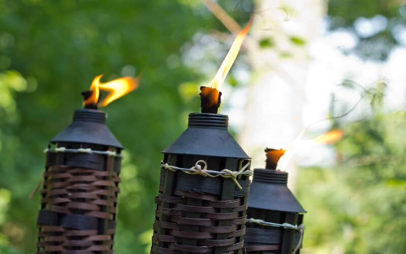 Three tiki torches lit outside to repel mosquitoes and other flying insects.