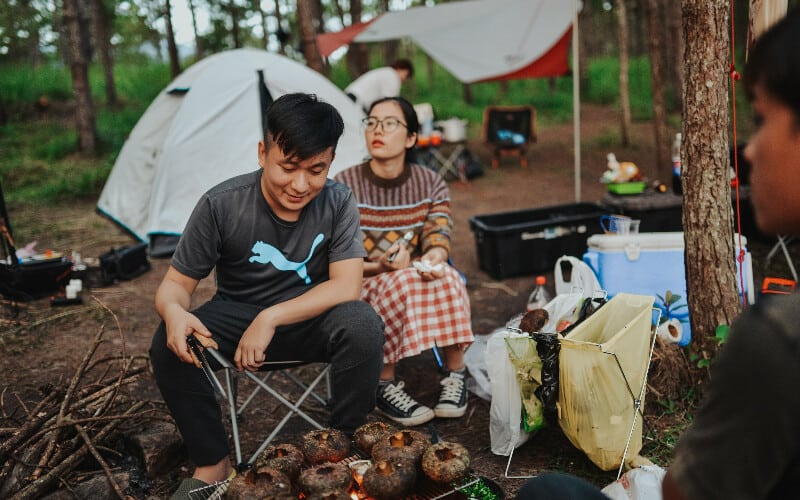 A group of people gathered around a campfire grilling food on a camping trip.