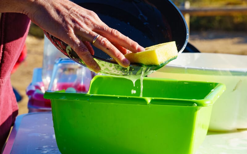 A close up of a woman's hands washing a pan at a campsite.