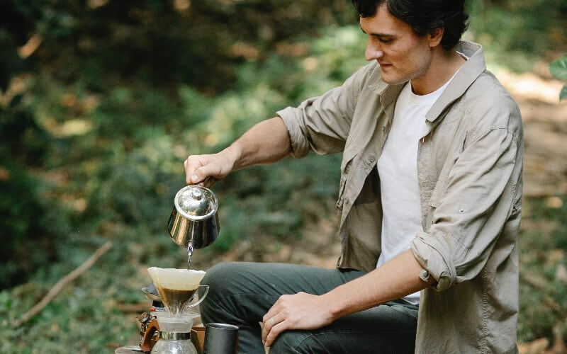 A man pouring water for coffee from the best camping water containers.