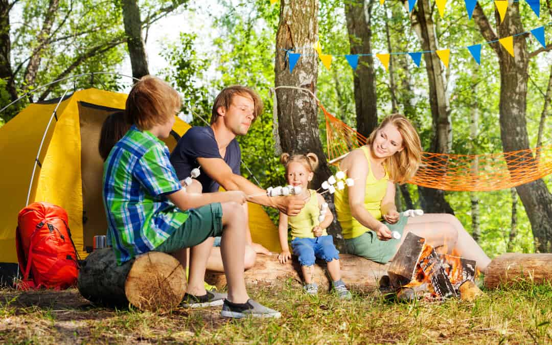 A man and his wife camping with their kids and roasting marshmallows near their tent.