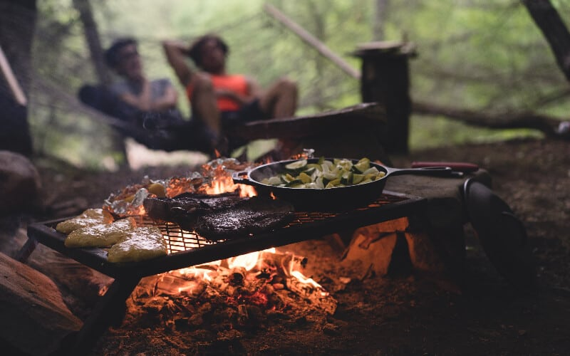 Food cooking on a grill over a campfire with two people in a hammock in the background.