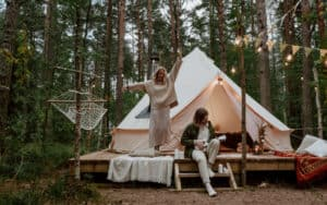 A man playing a ukulele while a woman dances in front of their tent on a glamping trip.
