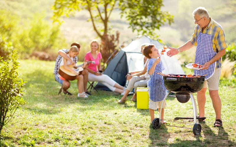 A grandson and his grandfather grilling food for the family in the background on their camping trip.