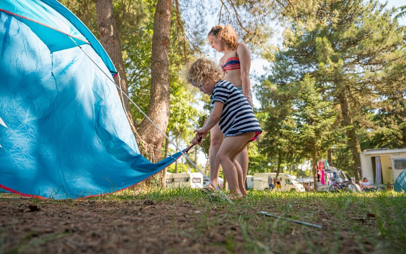 A young girl helping her family set up the tent at their campsite.