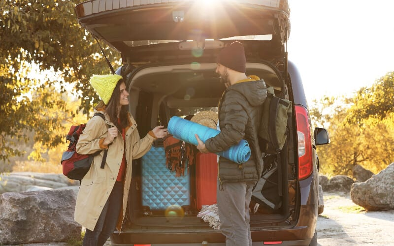 A young couple loading their hatchback while packing for their camping trip.