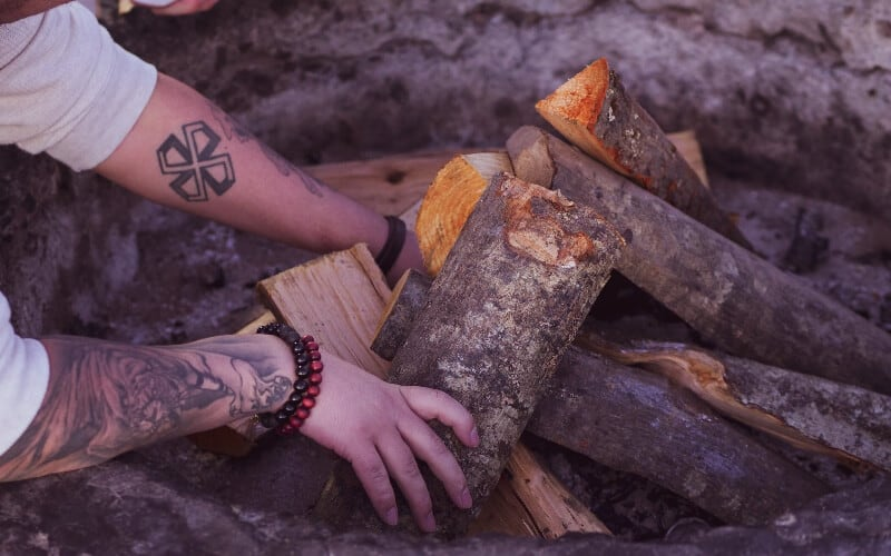 Closeup of a man's hands building a campfire.