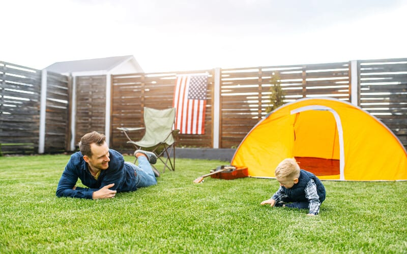 A father and son practicing camping in their backyard with a tent, chair, and guitar.