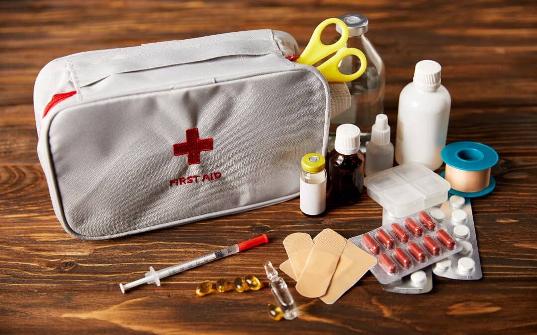 A camping first aid kit displayed on a wooden table.