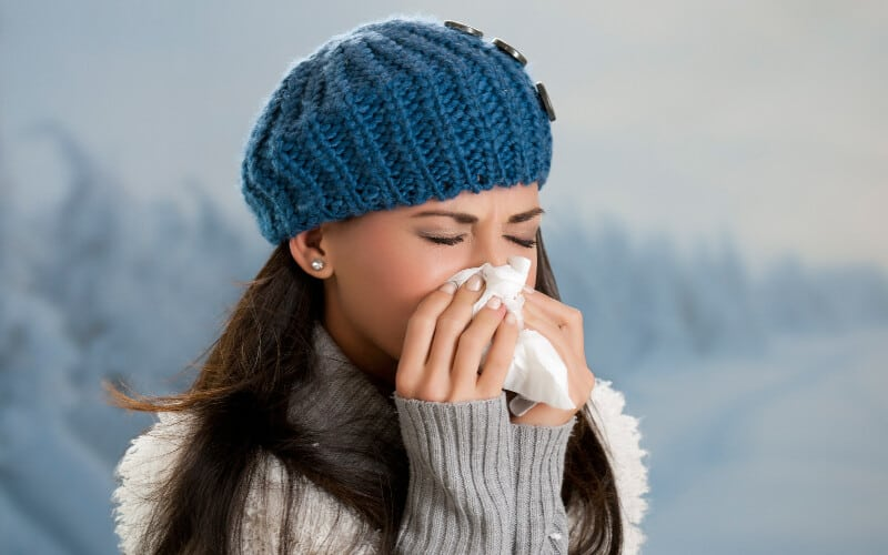 A woman with flu symptoms sneezing into a tissue in winter.