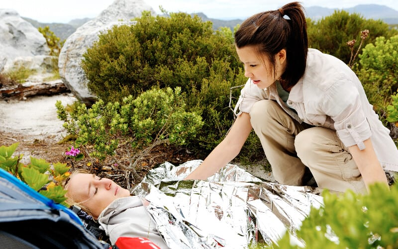 A woman puts an emergency blanket on another woman after a hiking accident.