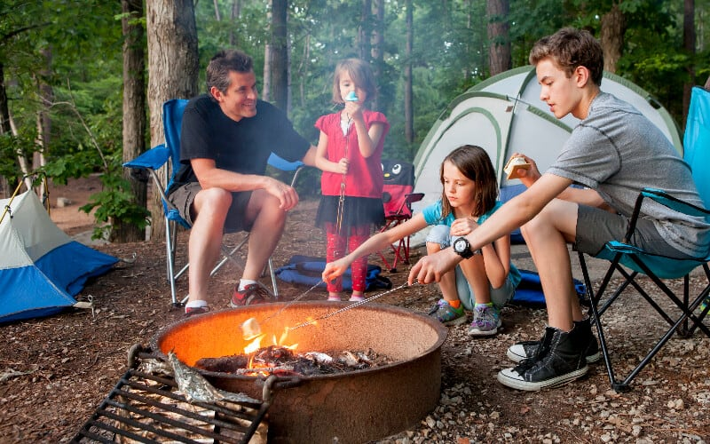 A father roasting marshmallows with his children around a campfire.