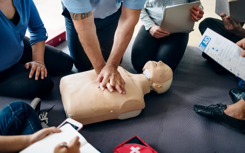 Man teaching CPR on a dummy during a first aid training course.