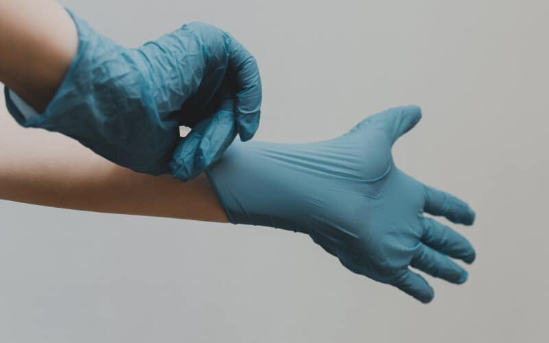 Close up of a person putting disposable medical latex gloves on.