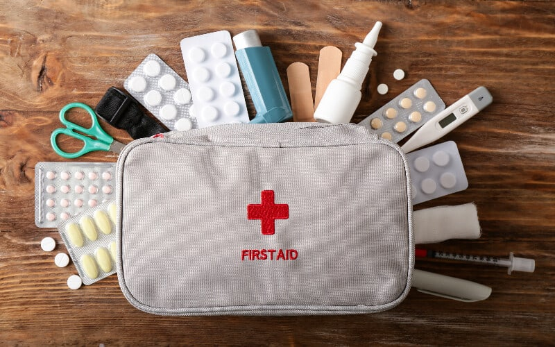 A first aid kit with miscellaneous medical items spread around it.