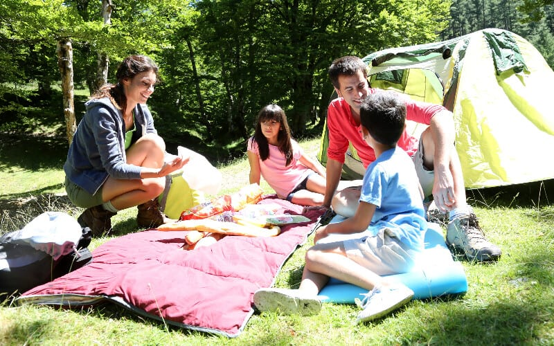 Parents and their children sitting down in front of their tent, enjoying their camping trip.