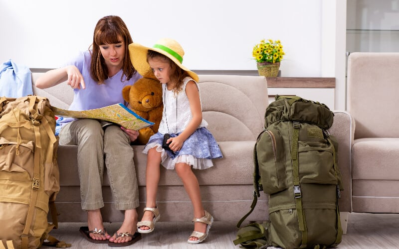 A mother and her daughter sitting on the couch, looking at a map and planning their camping trip.