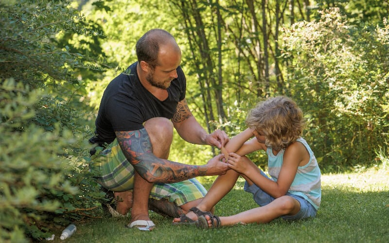 A father putting a bandage on his child's scraped elbow.