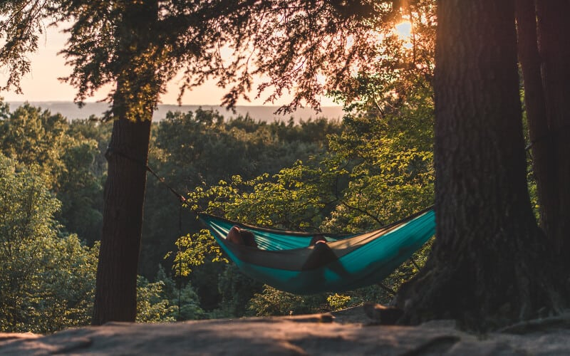 A man relaxing in his hammock on a hilltop as the sun begins to set.