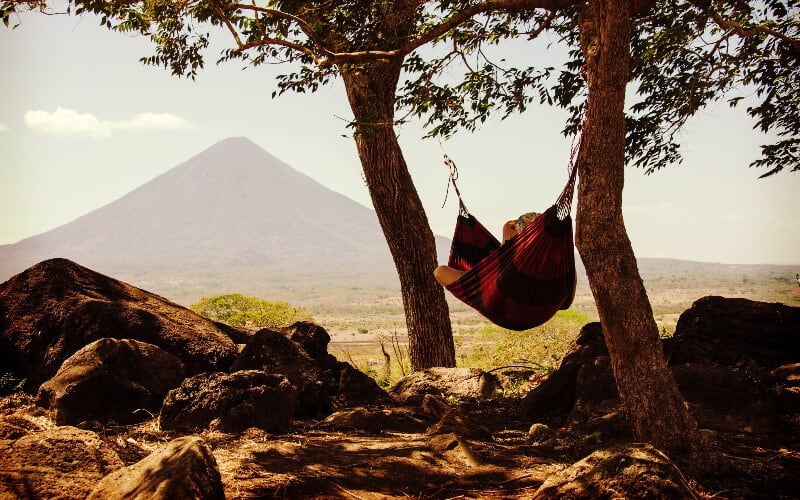 A person relaxing in a hammock between two large trees with a mountain in the distance.