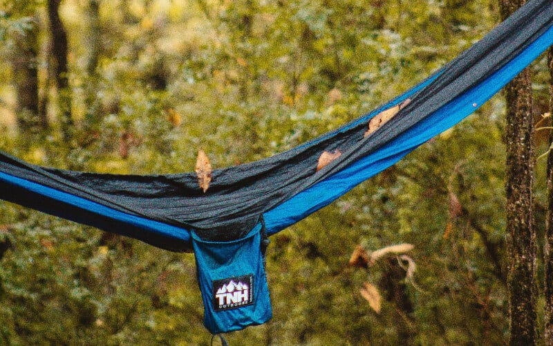 A close-up picture of leaves falling on an empty nylon hammock.