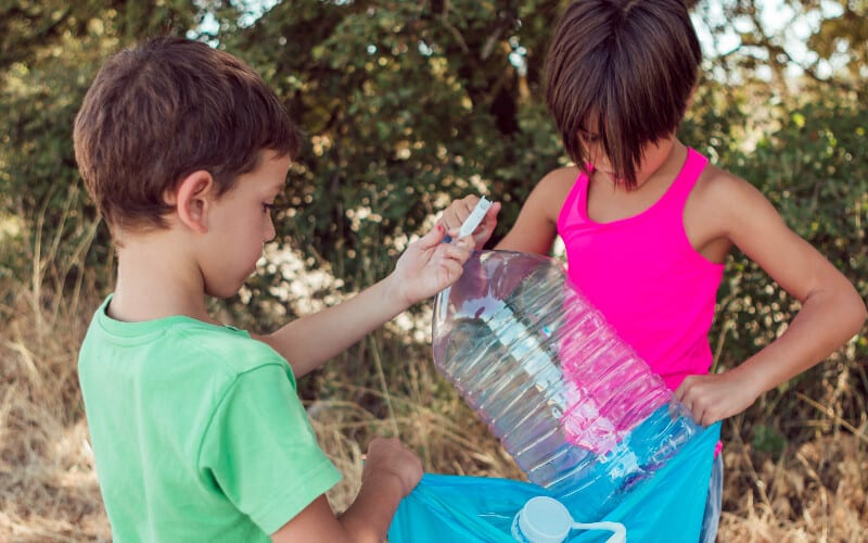 Two boys cleaning a water bottle from their campsite before leaving.