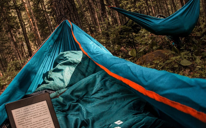 Reading a Kindle while relaxing in a hammock in the woods.