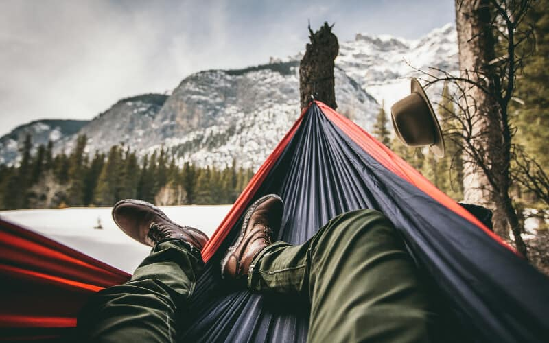A person's legs pointing diagonally across their hammock with mountains and trees in the background.