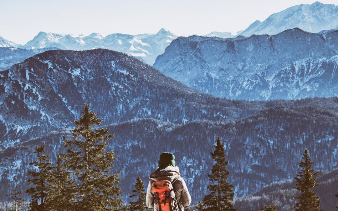 A hiker looking out at the Alps mountains.