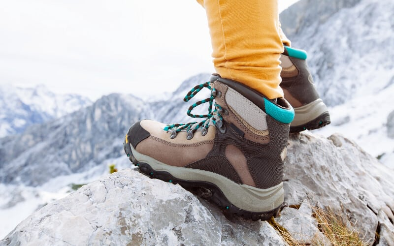 Close up of a woman's hiking boots on a mountain trail.