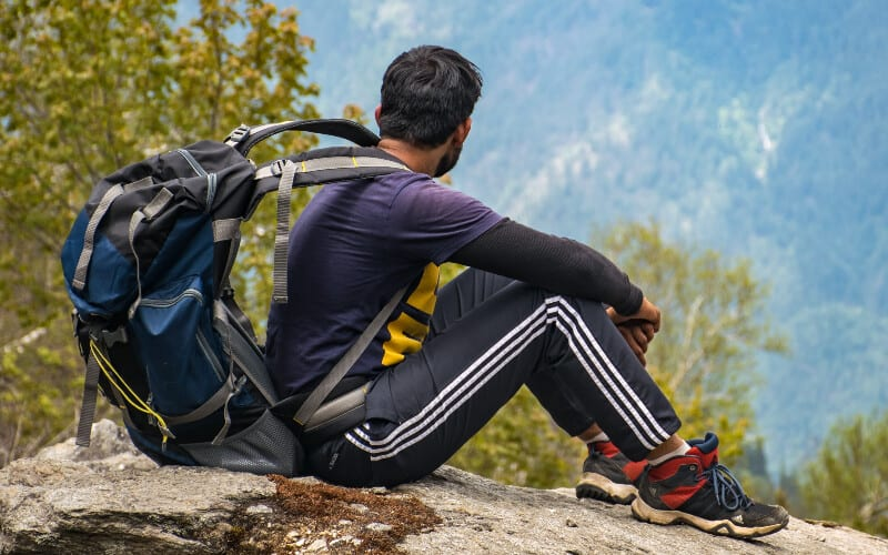 A man wearing hiking clothing with a backpack looking out over a valley.