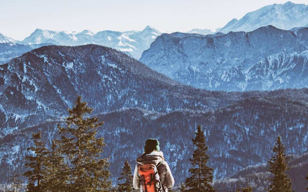 Hiking for Beginners: A hiker looking out at the Alps mountains.