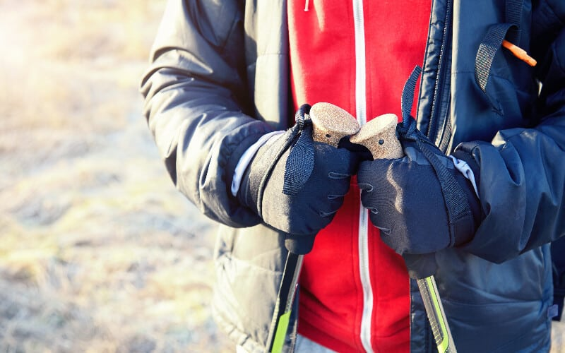 Close up of a man wearing hiking gloves holding trekking poles.