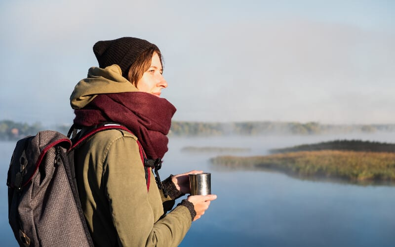 A woman staying warm with her hiking scarf while sipping a warm drink and overlooking a foggy river.