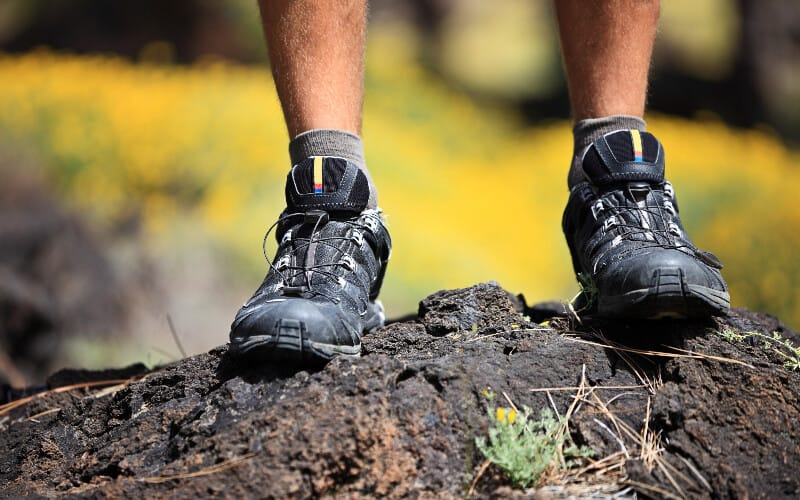 Close up of a man's hiking shoes on a rock.