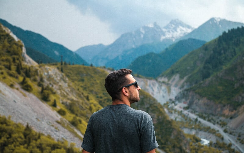 A man wearing sunglasses looking out over a valley during a hike.